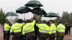 Police officers hold umbrellas to cover cameramen from the rain during a press conference at a Police Academy in Sibate, Colombia