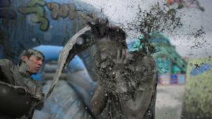 Man throwing a bucket of mud over someone
