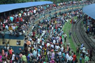 Passengers board a train at the railway station in Dhaka, Bangladesh