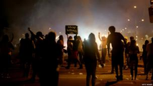 Demonstrators react as police fire tear gas at them as they protest the shooting death of Michael Brown in Ferguson, Missouri, 17 August 2014