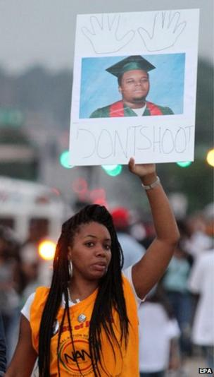 Demonstrators hold signs as protests continues after the shooting death of Michael Brown in Ferguson, Missouri, 17 August 2014