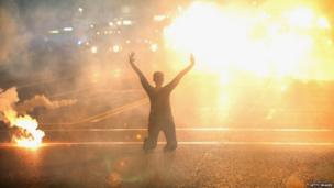 Tear gas envelops a woman kneeling in the street with her hands in the air after a demonstration over the killing of teenager Michael Brown by a Ferguson police officer in Ferguson, Missouri, 17 August 2014