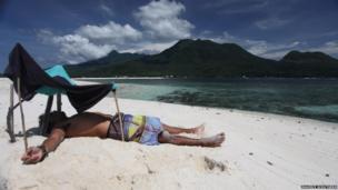 Man under shelter on a beach