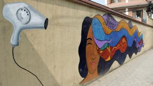 Street art of woman drying her colourful hair