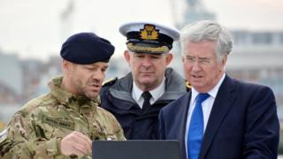 Military personnel show Michael Fallon work to dredge Portsmouth harbour.