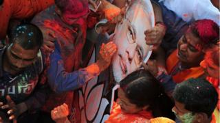 Indian supporters of the Bharatiya Janata Party (BJP) celebrate outside the party office as state assembly votes are counted in Lucknow on March 11, 2017.