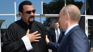 Russian President Vladimir Putin (R) speaks with US action movie actor Steven Seagal (L)