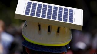 A man wears a solar panel hat at a rally in Adelaide, Australia, 29 November