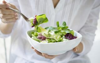 Detail of woman eating salad