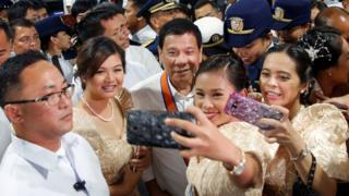Philippines President Rodrigo Duterte is having his pictures taken with three girls as they attend a ceremony