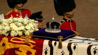 A diamond-encrusted crown bearing the Koh-I-Noor Diamond lies on a coffin bearing the Queen Mother in April 2002