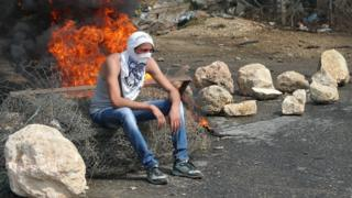 A Palestinian student from Palestine Polytechnic University sits during a protest against Israel near the Jewish settlement of Beit Hagai, October 2015
