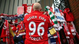 """Fan lays tribute on gate - his shirt says """"never ever forget - 96"""""""