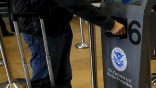 A traveller has his passport scanned as he passes through U.S. Customs and Immigration after using the Cross Border Xpress pedestrian bridge between San Diego and the Tijuana airport on the facility's opening day in Otay Mesa, California December 9, 2015.