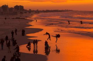 Palestinians make jumps on the beach during the sunset in Gaza City