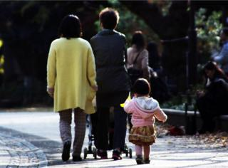 This picture taken on 12 December 2015 shows a family strolling at a park in Tokyo. Japan's top court will rule this week on a pair of 19th Century family laws that critics blast as sexist and out of touch