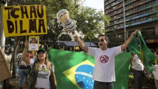 "A woman holds a sign that that reads in Portuguese; ""Bye Dilma"" next to a man holding a puppet in the likeness of Brazil's former President Luiz Inacio Lula da Silva, designed wearing a prison uniform, during a protest outside the hotel where Silva is attending the seminar, ""Democracy and Social Justice"", in Sao Paulo, Brazil, Monday, April 25, 2016."