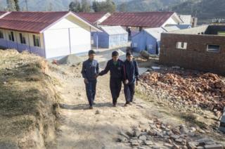 Saroj Raygiri (15) and Badal Ranamajar (14) help Sandesh up the hill to the school canteen