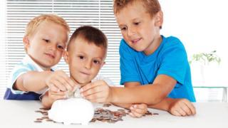 Boys putting coins into piggy bank