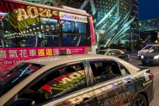 A taxi in which the Casino Lisboa is reflected stops in front of the Grand Lisboa (in background), in Macau in this February 17, 2015 file photo
