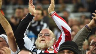 Man wearing Sunderland and Newcastle shirt