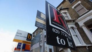 For sale signs stand outside properties