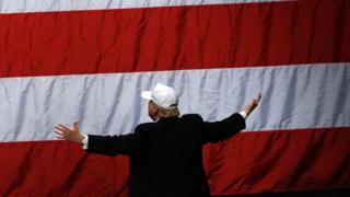 Donald Trump looks to the flag after he addressed supporters