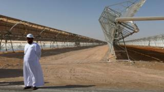 A man stands in front of rows of parabolic shaped mirrors at the Shams 1, Concentrated Solar Power plant, in al-Gharibiyah district on the outskirts of Abu Dhabi (17 March 2013)