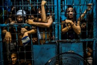 Inmates watch as drug suspects are processed inside a police station in Manila, Philippines