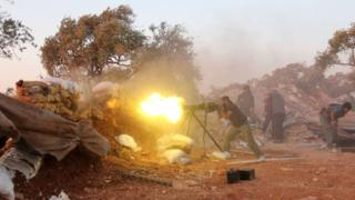 A rebel fighter fires heavy artillery during clashes with government forces and pro-regime shabiha militiamen in the outskirts of Syria's northwestern Idlib province