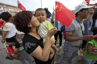 A woman kisses a baby after Beijing was announced as the host city for the 2022 Winter Olympics at the ski resort region of Chongli where the Nordic skiing, ski jumping, and other outdoor Olympic events will be held in northern China's Hebei province Friday, 31 July 2015.
