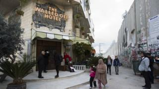 """People pass by the """"The Walled Off Hotel"""" and the Israeli security barrier in the West Bank city of Bethlehem, Friday, March 3, 2017."""