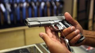 A man chooses a gun at the Gun Gallery in Glendale, California, 18 April 2007.