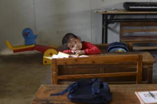 A student rests his head on a table inside a classroom of Dalu primary school in Gucheng township of Hefei, Anhui province, China, 8 September 2015.