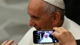 someone takes a photo of the pope with their mobile