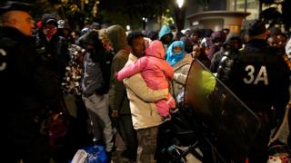 Migrants wait before entering buses