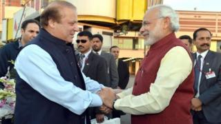 A handout photograph released by the Indian Press Information Bureau (PIB) on 25 December 2015 of Indian Prime Minister Narendra Modi (R) being welcomed by the Prime Minister of Pakistan, Nawaz Sharif (L), at the airport in Lahore, Pakistan, 25 December 2015