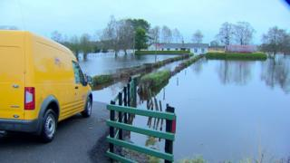 A Rivers Agency van sits at the end of a lane to a house surrounded by flooded fields