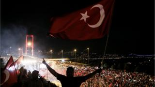 Citizens wave Turkish Flags during a march towards Bosphorus Bridge to protest failed military coup attempt and to show solidarity with the Turkish government in Istanbul.