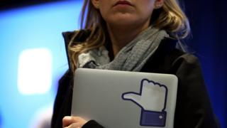 """woman holding laptop with Facebook """"thumbs up"""""""
