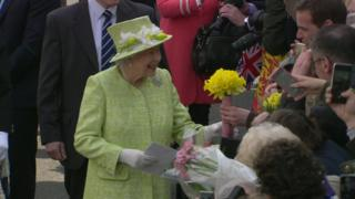 Queen Elizabeth II accepting a bouquet of daffodils