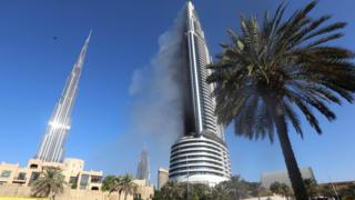 Plumes of smoke rise from the 63-storey Address Downtown hotel and residential block near the Burj Khalifa, a day after the hotel caught fire on New Year's Eve,