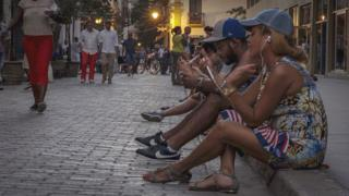 People use public WiFi to connect their devices in a street of Havana