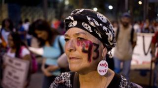 A woman with the number 43 painted on her face, referring to the 43 missing students from a rural teachers college, participates in a march in Mexico City, Thursday, Nov. 26, 2015