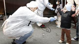 A child being checked for radiation in Fukushima prefecture following the nuclear disaster