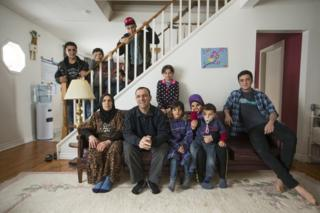 The inside Al Jasem family pose for a picture starting left to right on the couch, Mother Sawsan and father Abdel Malek, their kids, Walaa, Alaa, Khitam, Fadl, and Ramaz, and standing on the staircase left to right, Sleiman Abdel Malek, Madjid, Bachar, and Ahmad, inside their temporary home in Picton, Ontario, Canada,