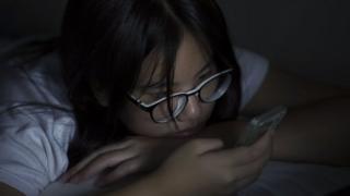 Akşam yatakta cep telefonunu kontrol eden bir genç kız