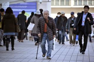 An elderly man walks with a stick in Yokohama, near Tokyo, Japan, 26 February 2016
