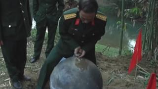 An official in uniform trying to lift one of the orbs