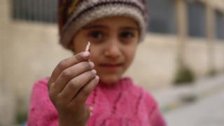 A girl shows a sniper's bullet found in her schoolyard in rebel-held Douma, a suburb of Damascus, 12 April 2016